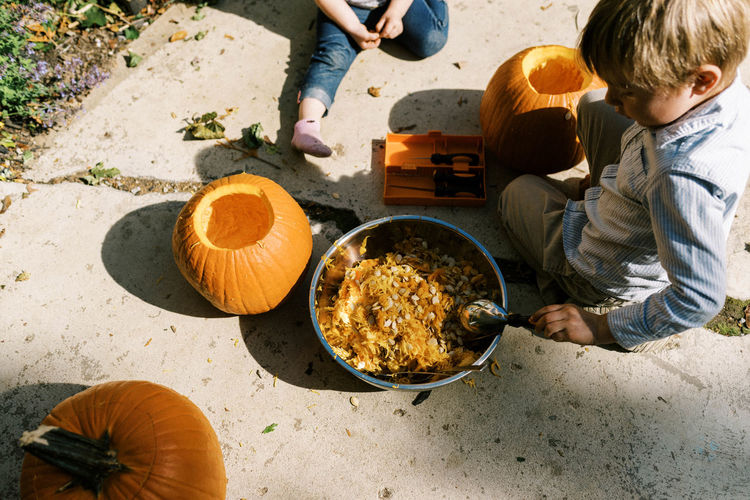 High angle view of people sitting by pumpkins