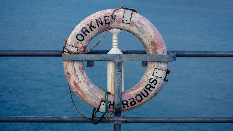 Close-up of lifebelt hanging on railing of boat