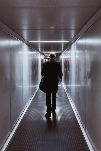 Rear view of man walking on illuminated corridor