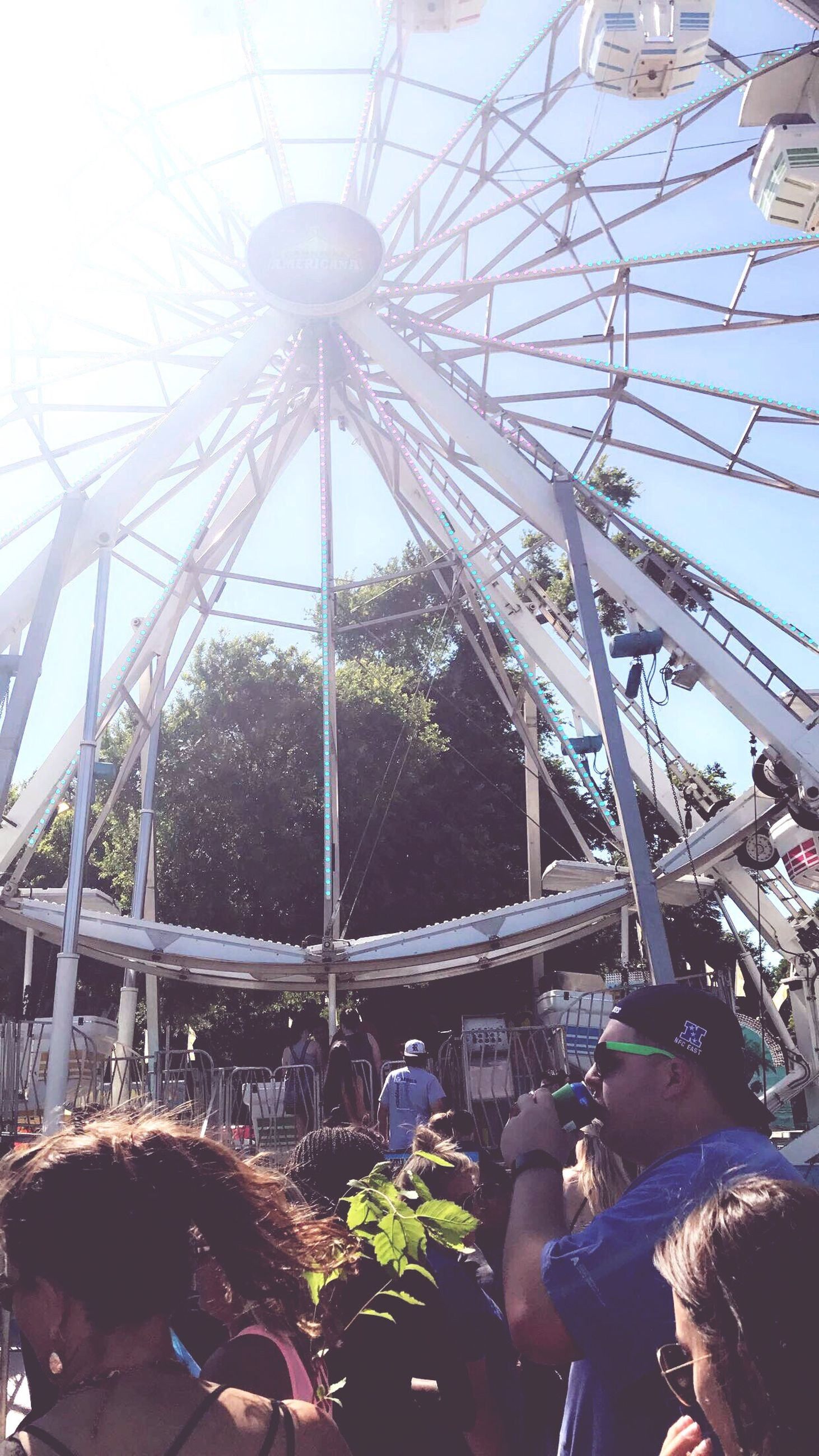 real people, leisure activity, amusement park, large group of people, arts culture and entertainment, fun, childhood, day, low angle view, lifestyles, outdoors, men, amusement park ride, togetherness, group of people, women, friendship, crowd, sky, people