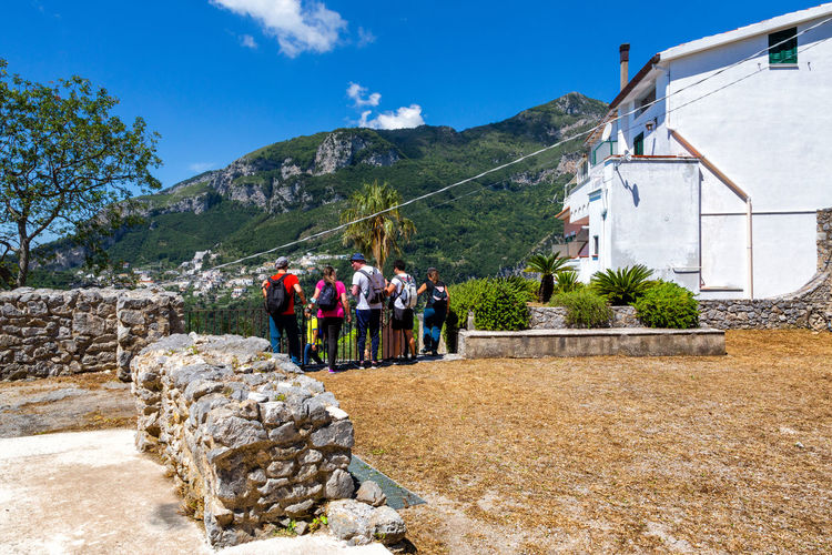 Group of people outside building against mountain range