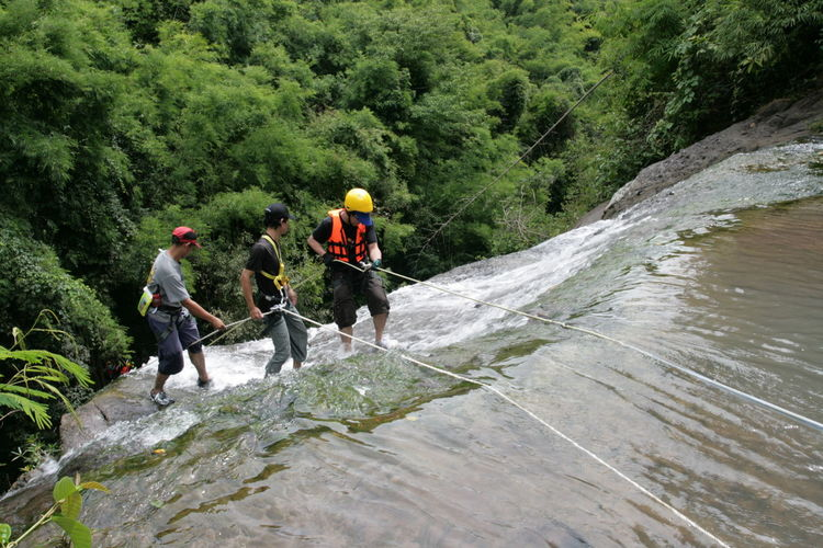 People climbing on waterfall in forest