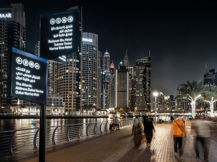 People on illuminated modern buildings in city at night
