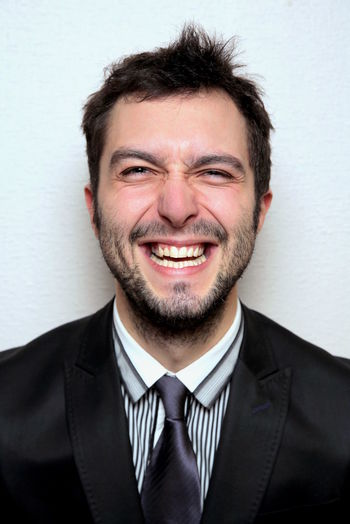 Portrait of smiling young businessman against wall