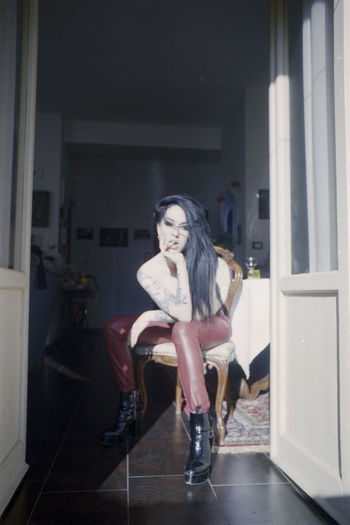 Portrait of woman sitting on chair at home