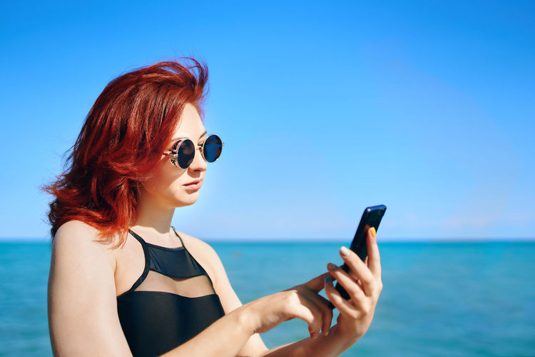 Young woman using mobile phone against sea