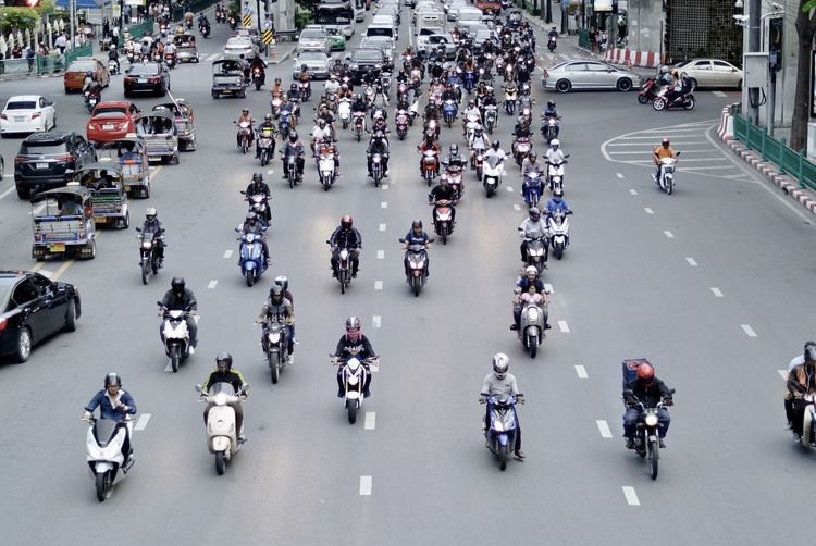 High angle view of motor scooters moving on road
