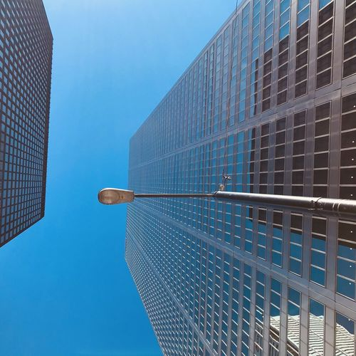 Low angle perspective of glass skyscrapers with a street lamp overhead