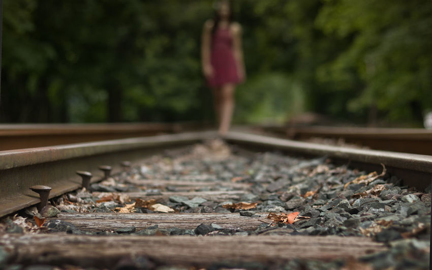 Close-up of railroad track, female in background.