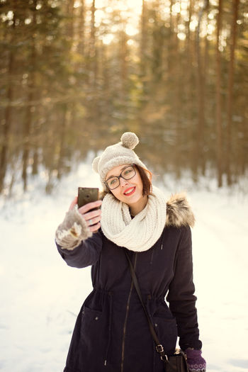 Cold Temperature Day Focus On Foreground Forest Friendship Front View Happiness Knit Hat Leisure Activity Lifestyles Nature Outdoors Real People Smiling Snow Standing Togetherness Tree Two People Warm Clothing Weather Winter Women Young Adult Young Women