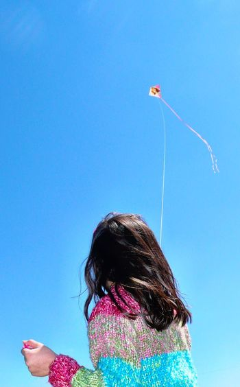 Rear view of woman flying kite in clear blue sky