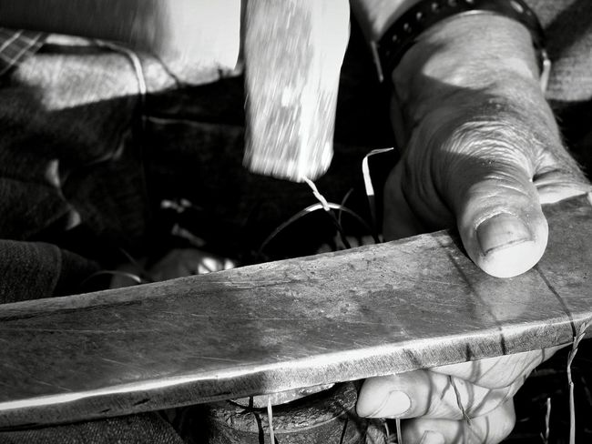 Close-up Day Feather  Focus On Foreground Hammer Hand Tool Human Body Part Human Hand Indoors  Manual Worker Men Metal Industry Occupation One Person People Real People Reap Scythe Whether Wood - Material Work Tool Working Workshop