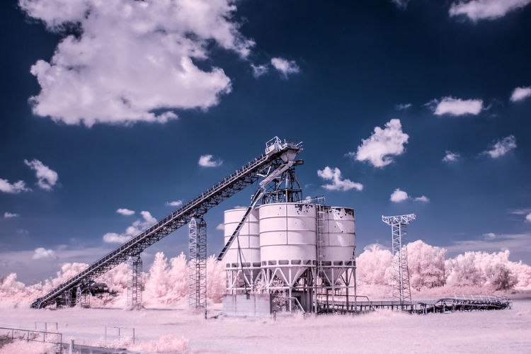 Infrared image of storage tanks against sky