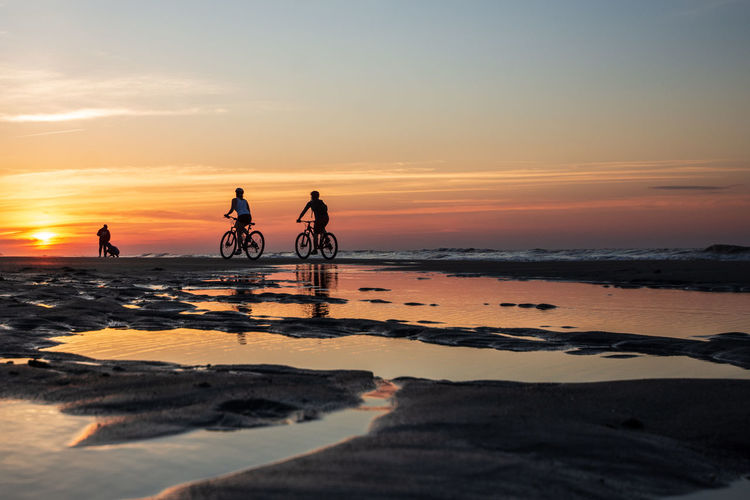 Peddling into the Weekend Sunset Sky Water Beach Sea Real People Beauty In Nature Orange Color Land Scenics - Nature Lifestyles Leisure Activity Silhouette Cloud - Sky Tranquility Nature Group Of People Men People Horizon Over Water Outdoors Sunrise Bicycle Reflection Ocean Sun Exercise