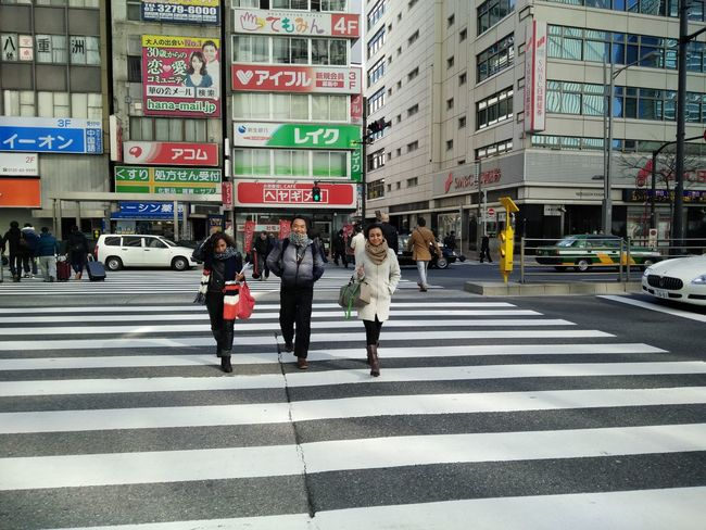 Three Indonesian people crossing the street in Tokyo Architecture Building Built Structure City City Life City Street Crosswalk Day Group Of People Leisure Activity Lifestyles Medium Group Of People Outdoors Pedestrian Road Road Marking Road Sign Street Zebra Crossing