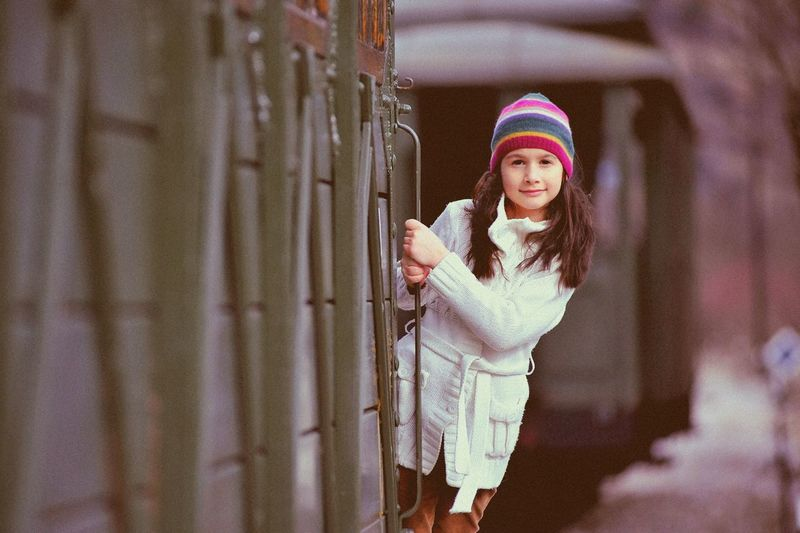 The girl on the train. Cap Casual Clothing Childhood Day Elementary Age Front View Girls Leisure Activity Lifestyles Looking At Camera One Person Outdoors People Portrait Real People Retro Retro Style. Smiling Standing Warm Clothing Young Adult Young Women