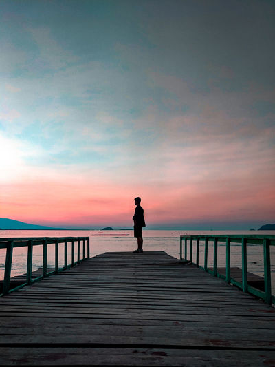 Silhouette man standing on pier by sea against sky during sunset