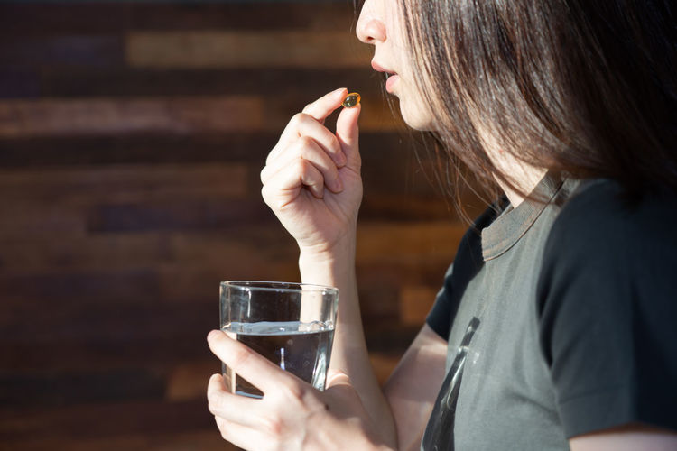 Midsection of a woman drinking glass
