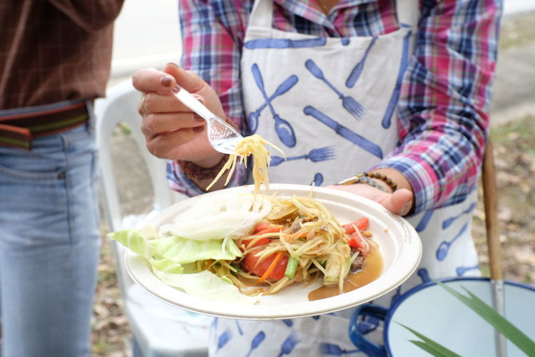 Midsection of woman holding papaya salad