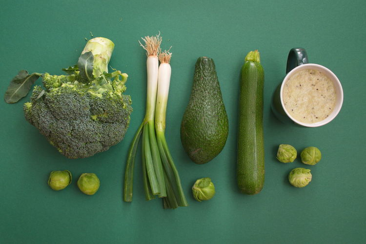 Food Food And Drink Healthy Eating Freshness Wellbeing Vegetable Studio Shot Still Life Indoors  Directly Above Colored Background No People Green Color Fruit Green Background High Angle View Variation Choice Broccoli Avocado Onion Cup Smoothie Diet Organic