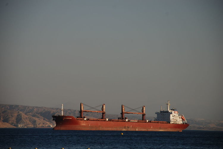 A large cargo ship anchored in the Gulf of Aqaba at Eliat, Israel Israel Middle East Container Ship Eilat Gulf Of Aqaba Transportation Water Nautical Vessel Sea Shipping  Cargo Container Anchored Outdoors Sky No People Ship Mode Of Transportation Freight Transportation Cargo Shipping  Logistics Business Sailing One Ship Large Ocean Ckear Sky Large Ship