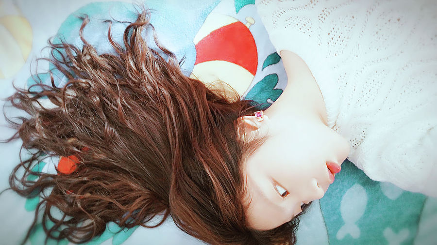 High Angle View Of Woman With Long Brown Hair Lying On Bed At Home