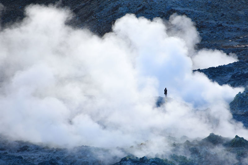 Scenic view of clouds by rock formation with person standing