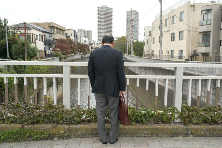 Rear view of man standing by railing against buildings