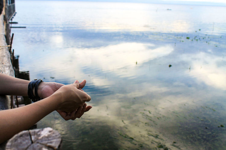 Human Hand Human Body Part Reflection Water Leisure Activity One Person Outdoors Sky Day People Close-up Adult Nature Adults Only Meditation Zen Tranquility Travel Beauty In Nature Real People Long Goodbye