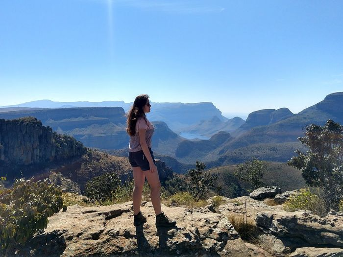 Side view young woman standing on cliff by mountains against sky