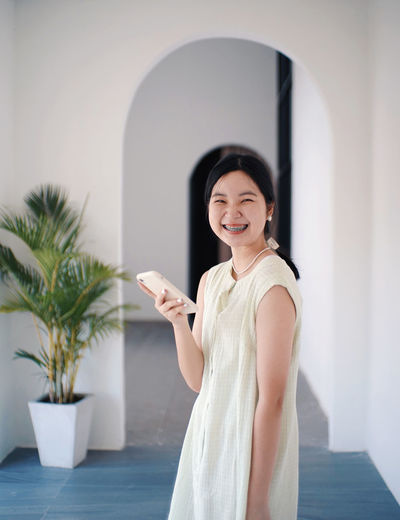 Young woman holding smart phone while standing on laptop
