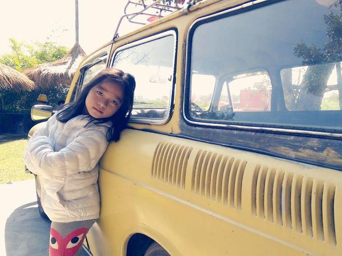 Portrait of girl standing against car