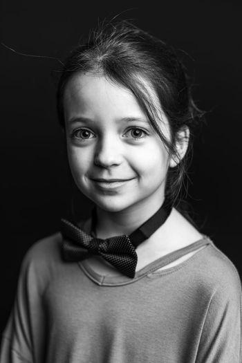 Portrait of girl smiling against black background