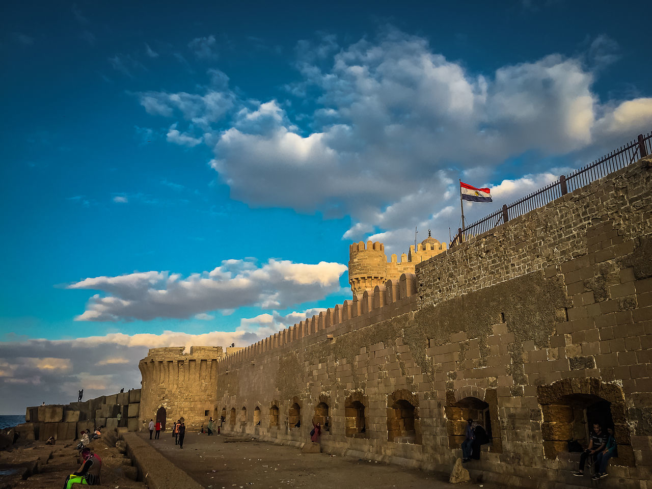 cloud - sky, history, architecture, built structure, sky, large group of people, building exterior, travel destinations, real people, tourism, day, ancient, flag, old ruin, outdoors, travel, low angle view, ancient civilization, women, men, pyramid, people