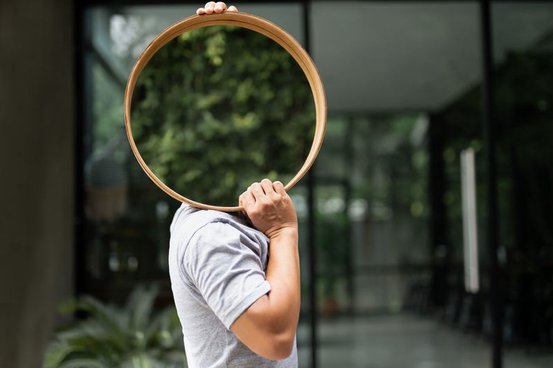 Midsection of man holding mirror