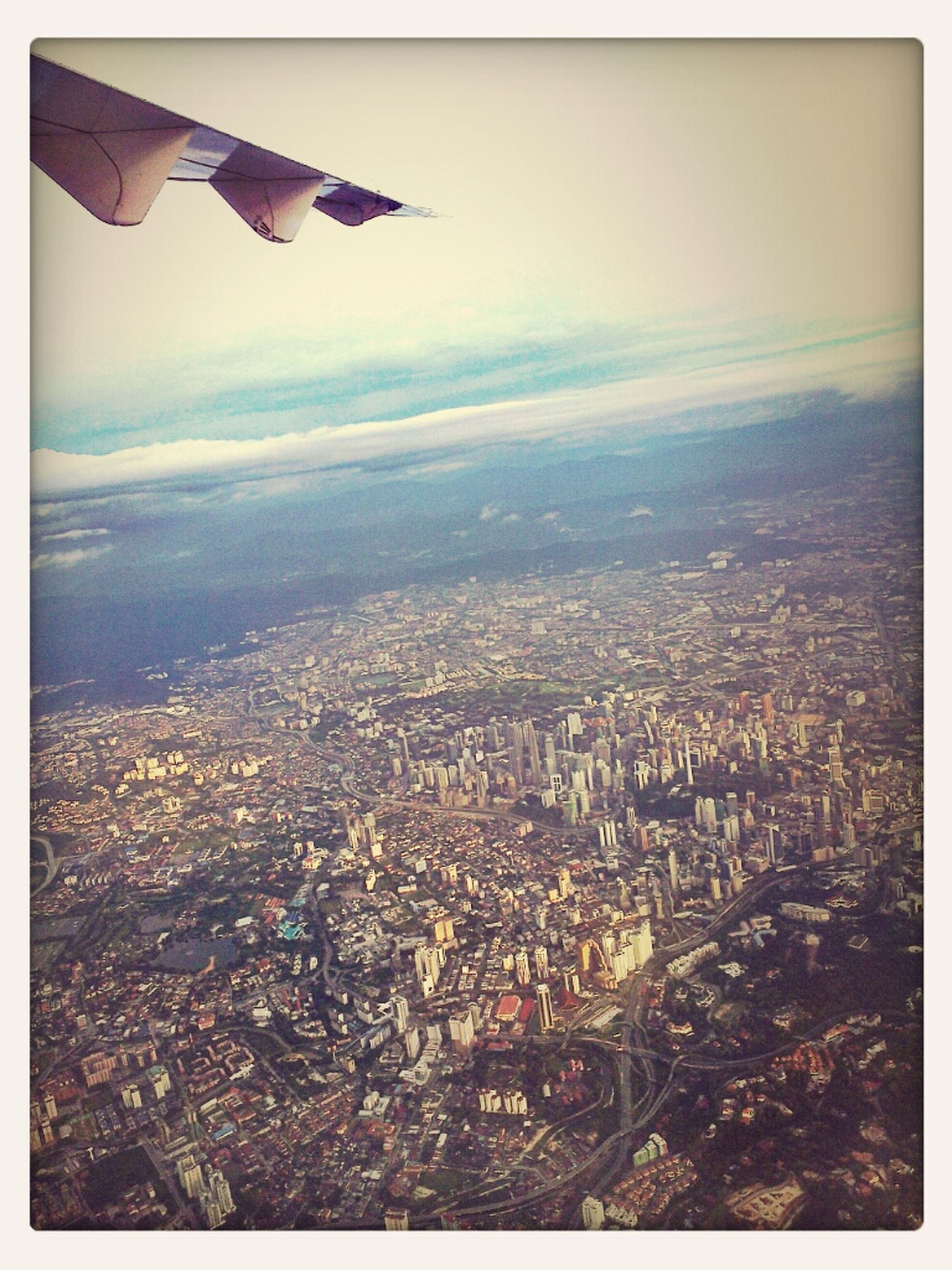 flying, aerial view, airplane, aircraft wing, air vehicle, sky, cityscape, mid-air, cloud - sky, city, part of, scenics, nature, beauty in nature, building exterior, outdoors, no people, landscape, cloud, blue
