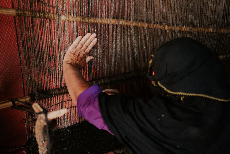 Rear view of woman working at loom
