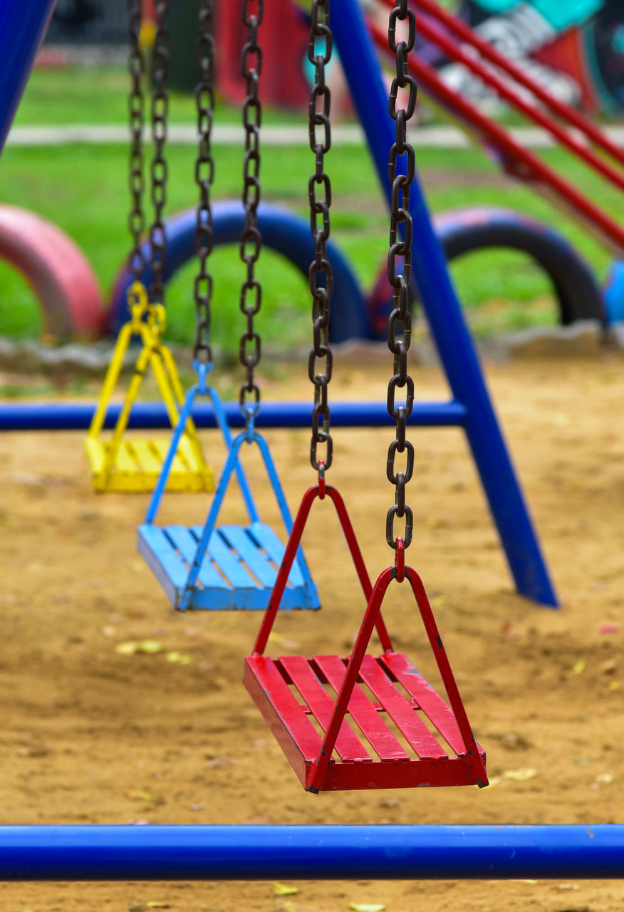 playground, childhood, outdoor play equipment, focus on foreground, park - man made space, metal, hanging, swing, chain, park, day, blue, empty, multi colored, absence, fun, close-up, jungle gym, outdoors