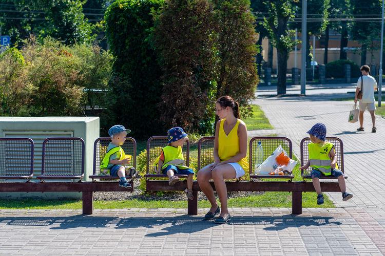 Woman and children in yellow reflective vests resting on a bench in the park. Children Kids Adult Bench Day Full Length Group Of People Leisure Activity Lifestyles Nature Outdoors Park Park Bench People Plant Real People Reflective Relaxation Safety Seat Sitting Sunlight Tree Vests Women