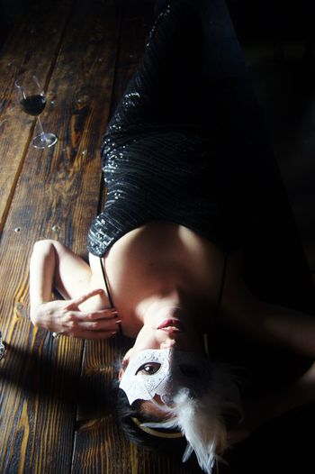 High angle view of woman wearing mask lying down on table