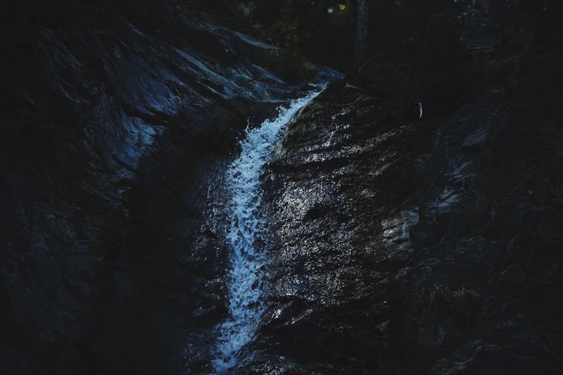 High angle view of stream flowing amidst rocks at night