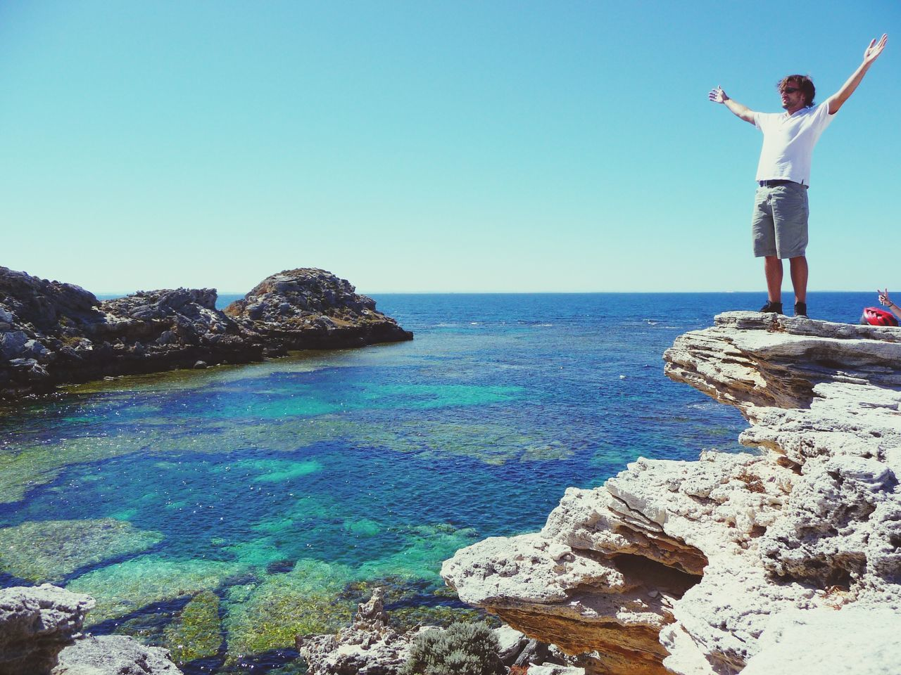 Man With Arms Outstretched Standing On Top Of Rock Formation At Sea Shore