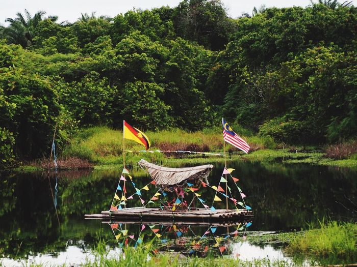 Flags and decoration on wooden raft moored at lake against trees