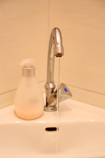 Close-up of water falling from faucet at bathroom sink