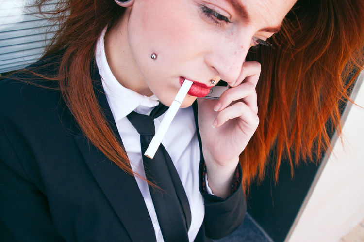 Close-up of businesswoman smoking while talking on smart phone