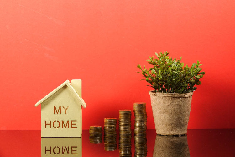 Saving Concept with coins stacked on a red background. Reflection Architecture Built Structure Car Close-up Coins On The Table Colored Background Communication Conceptual Copy Space Growth Housing Indoors  Medical Nature No People Number Plant Potted Plant Red Saving Sign Stethoscope  Still Life Studio Shot Text Wall - Building Feature Wood - Material