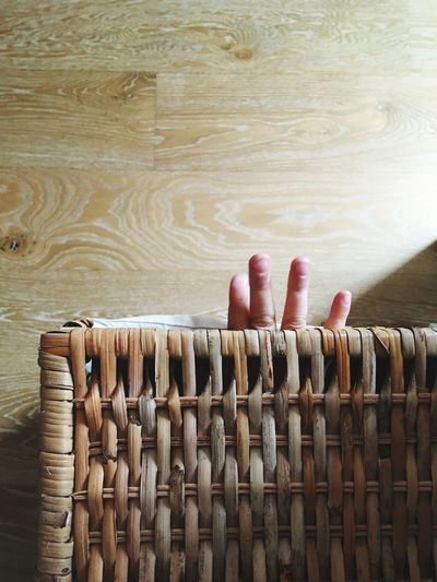 Cropped hand of baby in wicker basket at home