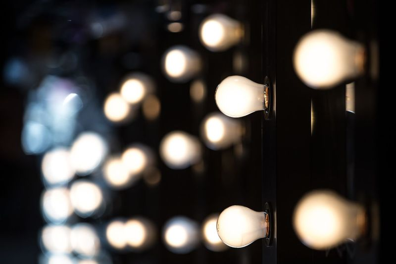Close-Up Of Illuminated Light Bulbs On Dressing Table At Backstage