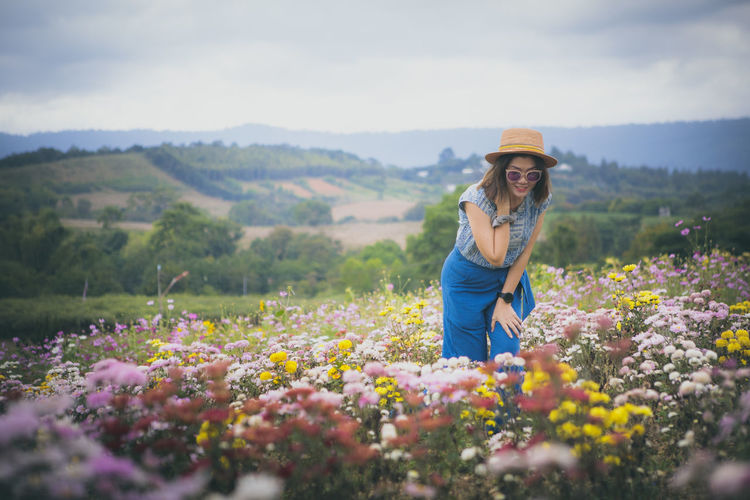 Woman standing by flowers on land against sky