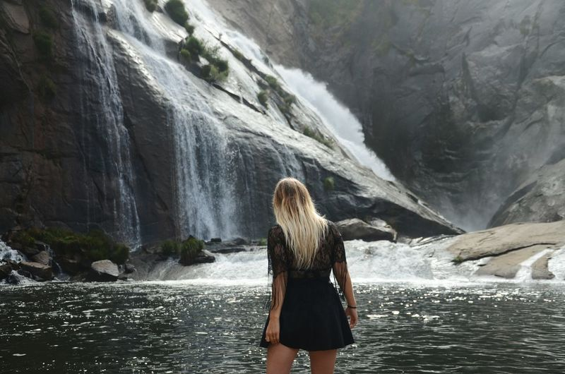 Rear view of woman standing by waterfall